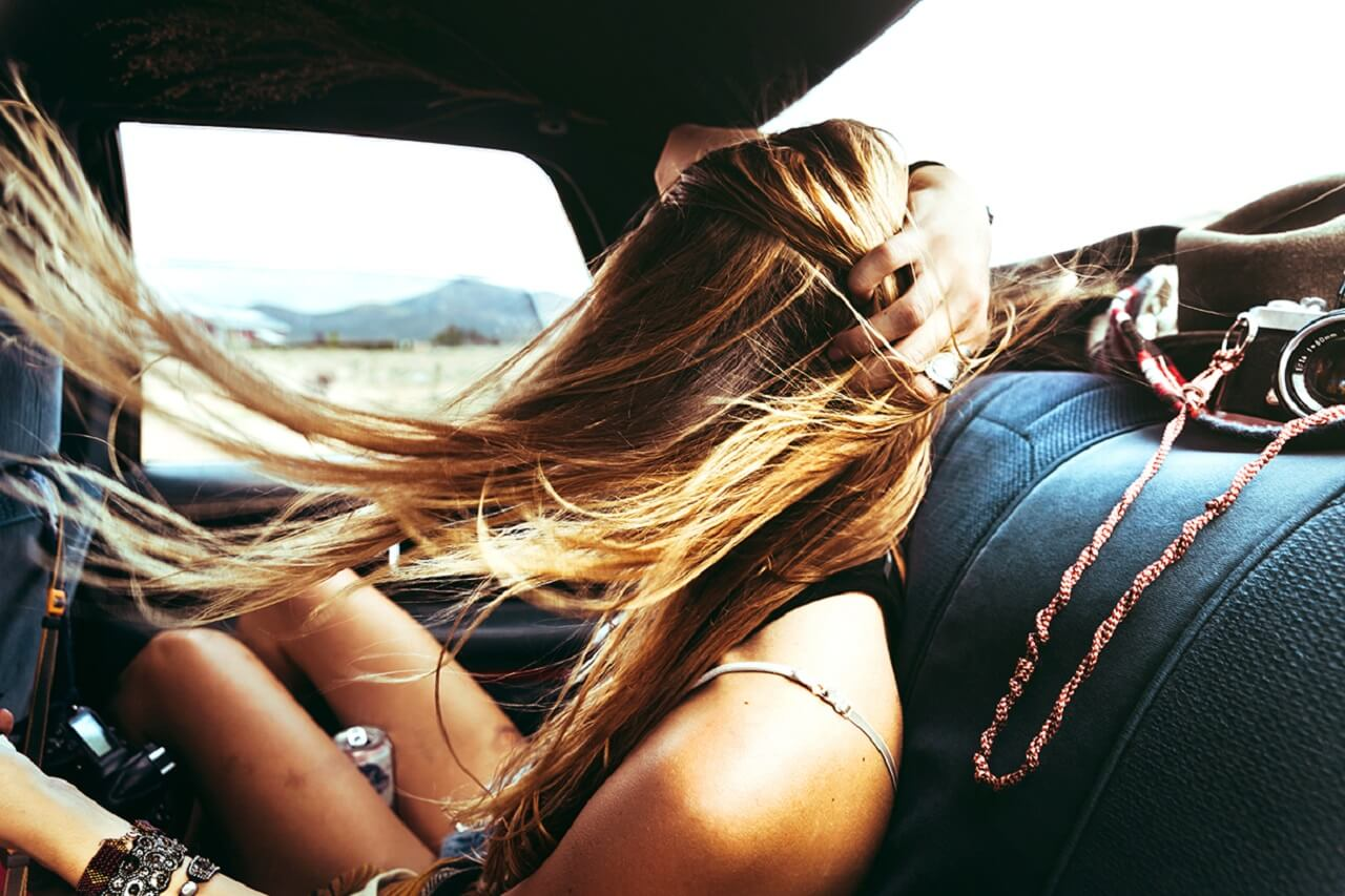 girl sitting in the back of the car