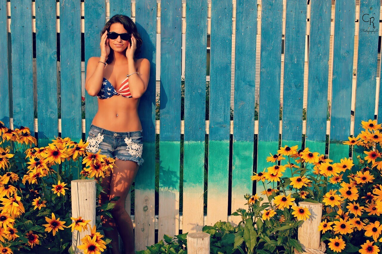 woman by the fence with flowers