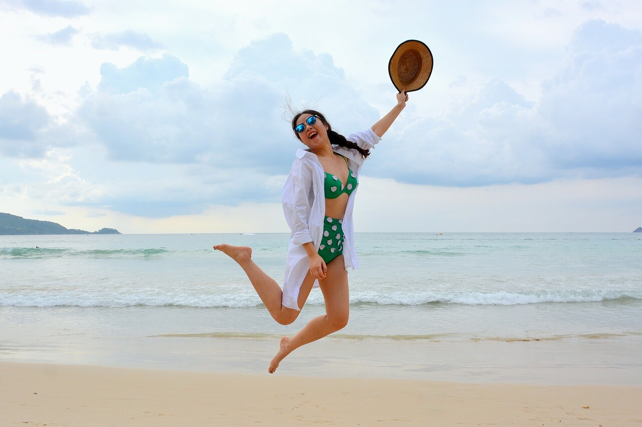 woman jumping up by the beach
