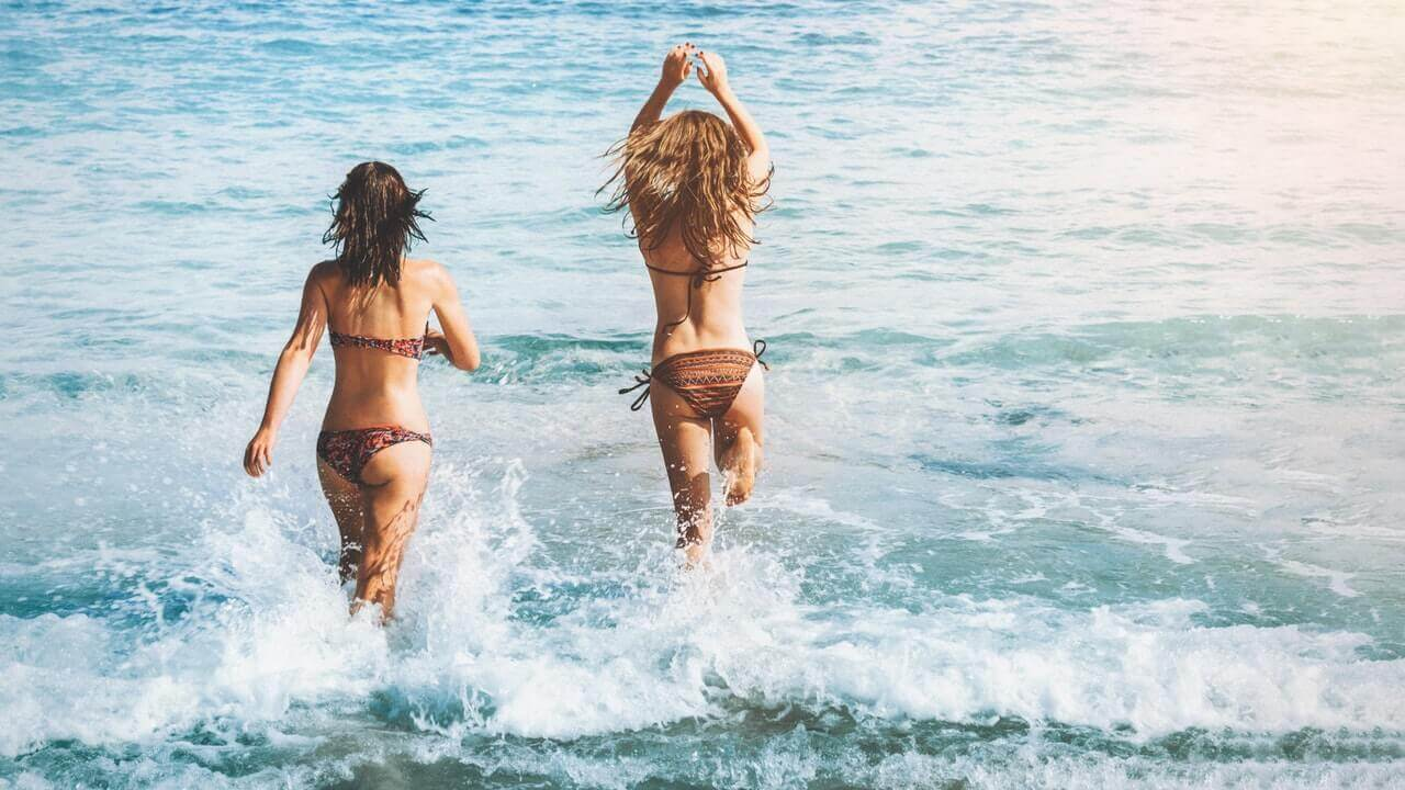 two women running in the sea