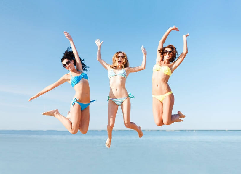 Women jumping in the air on the beach