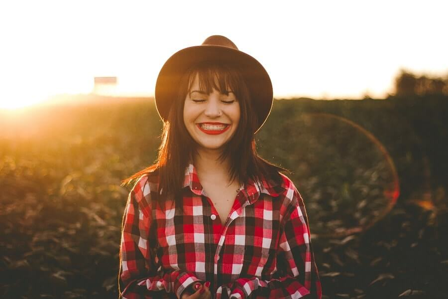 Girl with red lipstick smiling at sunset